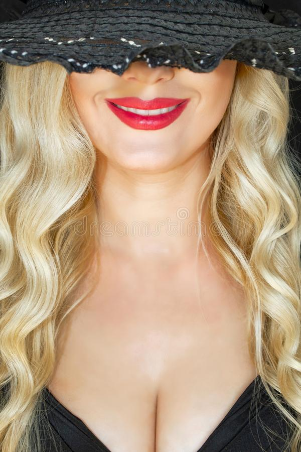 Porträt Schöne junge Blondine im schwarzen Hut mit decollete auf dunklem Hintergrund mysteriös lächelnd Nahaufnahme Helles Rot lizenzfreie stockfotos