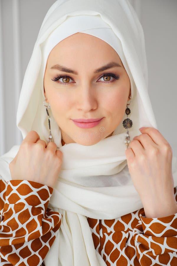 Portr?t sch?ne junge moslemische arabische Frau tragenden wei?en hijab, das Kamera betrachtet lizenzfreie stockfotografie