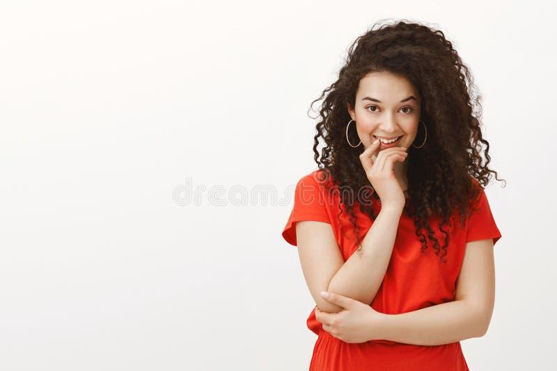 Porträt schönen flirty femenine Mädchens mit dem gelockten Haar, faszinierend lächelnd und halten Hand auf Ching und kreuzen lizenzfreie stockbilder