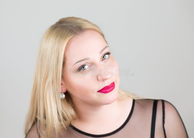 Porträt schönen jungen Blondine in einem glättenden schwarzen Kleiderabschluß oben stockfotos
