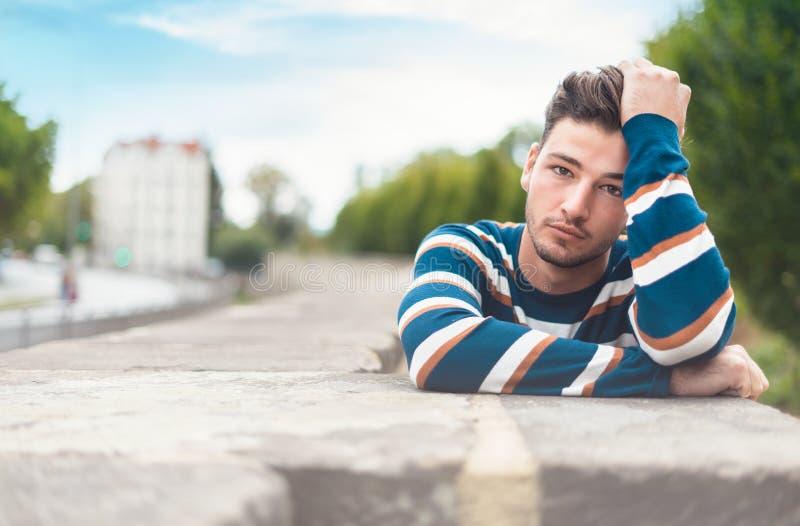 Porträt schönen youg Mannes mit seiner Hand auf dem Haar, das zur Kamera aufwirft lizenzfreie stockfotografie
