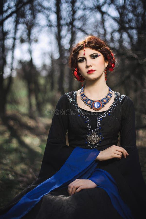 Porträt schöner mittelalterlicher Dame im feenhaften Wald stockbilder