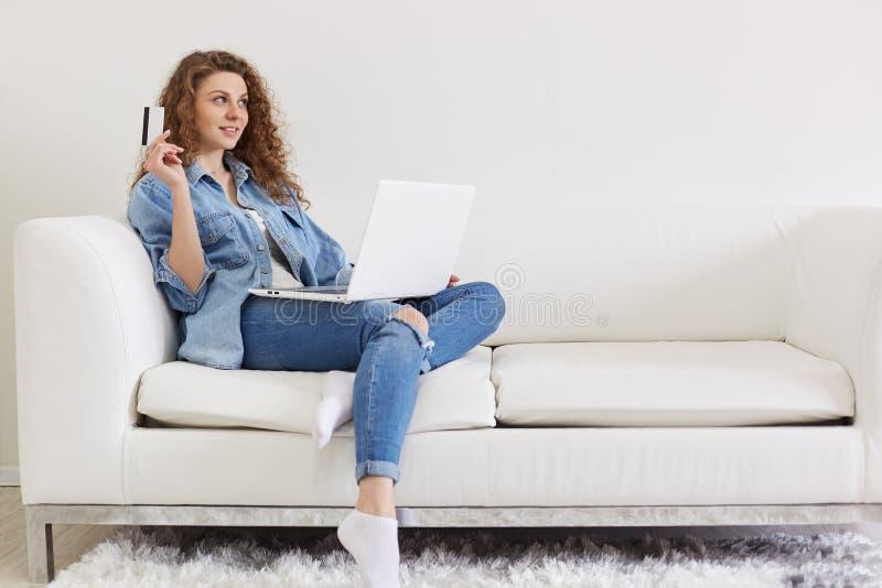 Porträt schöner positiver Dame, die beiseite, Hand mit Kreditkarte anhebend sucht und machen Pläne nach dem on-line-Einkaufen und lizenzfreies stockfoto