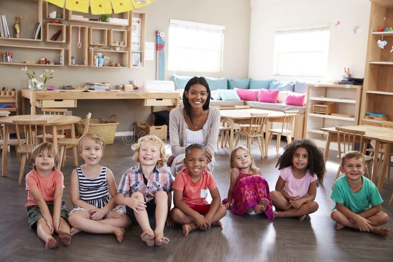 Porträt Schuldes klassenzimmers Lehrer-With Pupils Ins Montessori stockfotografie