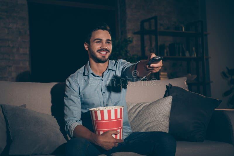 Porträt seines netten, fröhlichen, fröhlichen Brunet-Typen, der Urlaub verbringt auf Divan sehen Fernsehshow sitzen stockfotos