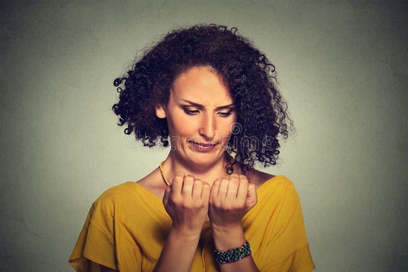 Porträt sorgte sich die Frau, welche die Handfingernägel betrachtet, die um Sauberkeit besessen sind lizenzfreie stockfotografie