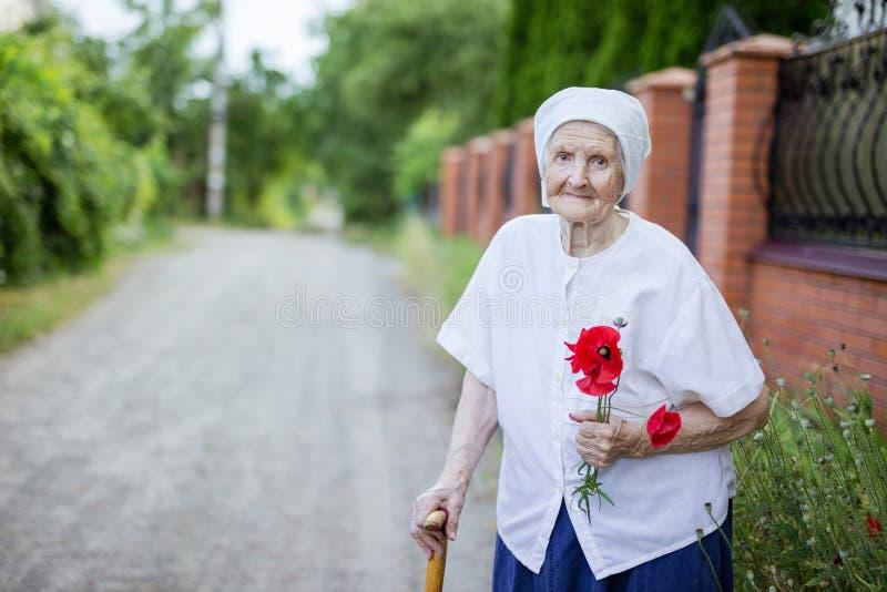 Porträt von älteren Frauenholding-Mohnblumenblumen stockfotografie