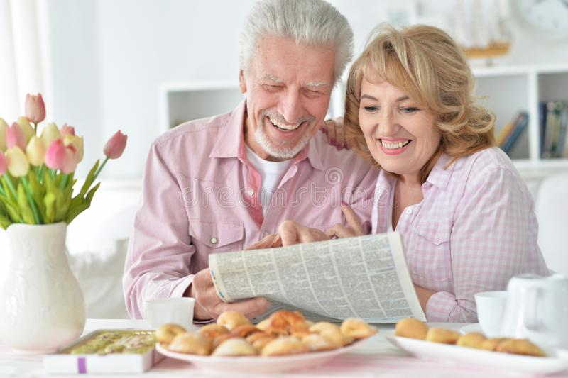 Portr?t von ?lteren Paaren mit Zeitung zu Hause stockbild