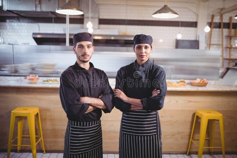 Porträt von überzeugten Jungen warten Personal in der schwarzen Uniform, die mit den Armen steht, die an der Kaffeestube gekreuzt lizenzfreie stockbilder