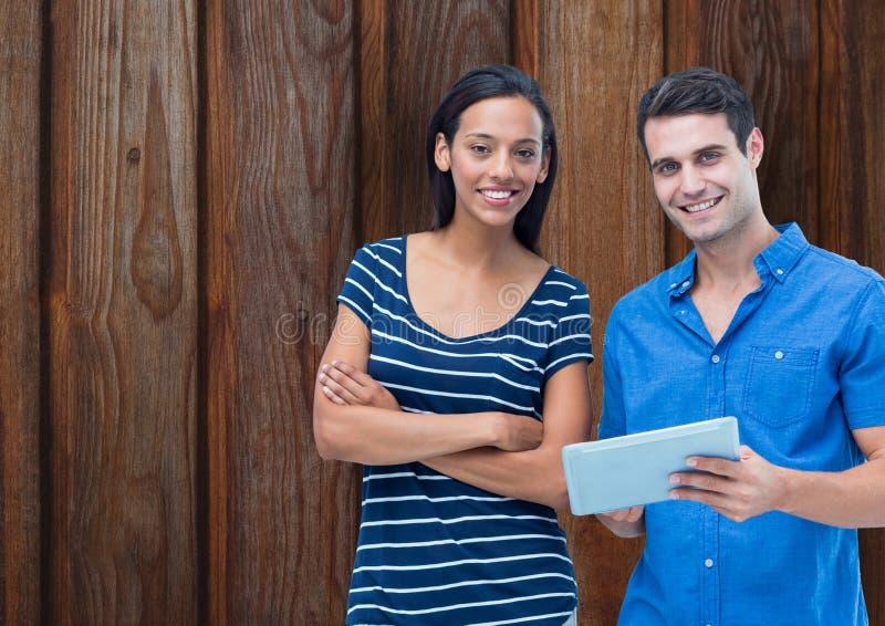 Porträt von überzeugten Paaren mit digitaler Tablette gegen hölzerne Wand lizenzfreie abbildung