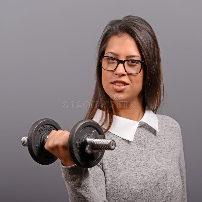 Porträt von anhebenden Gewichten der Geschäftsfrau gegen grauen Hintergrund stockfoto