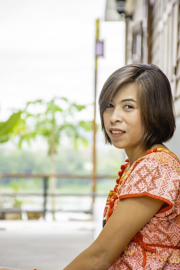 Porträt von Asean-Frau einen Eingeborenen der hölzernen Wand Nord-Thailand-Hintergrundes tragend lizenzfreie stockfotografie