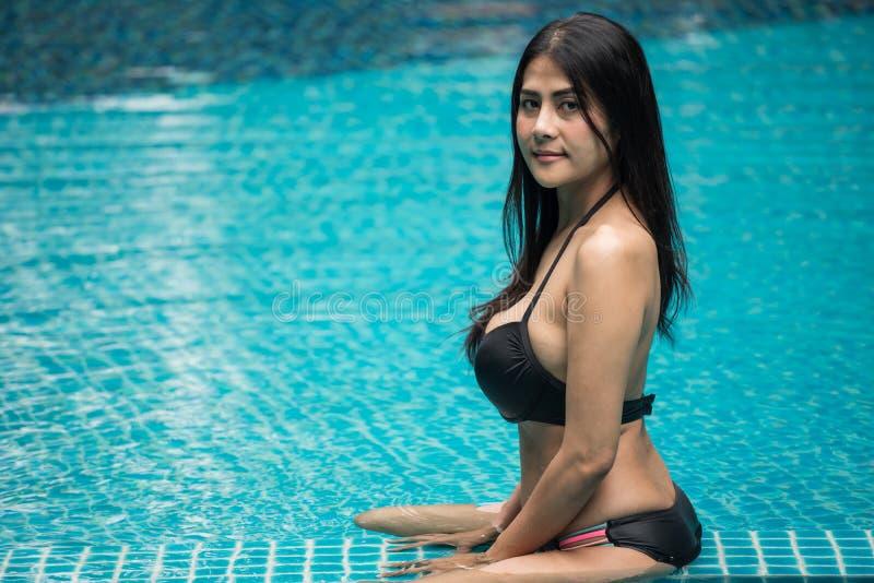 Porträt von asiatischem schönem bräunen Mädchen mit großen natürlichen Dummköpfen, schwarzen zweiteiligen Badeanzug am Swimmingpo lizenzfreie stockfotografie