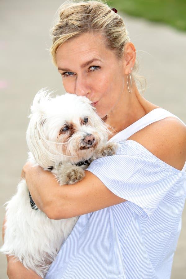 Porträt von Blondinen einen netten kleinen weißen Hund halten stockbilder