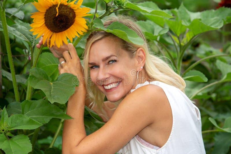Porträt von Blondinen im Garten mit Sonnenblumen lizenzfreies stockbild