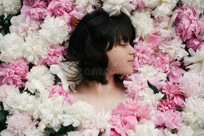 Porträt von boho Frau mit dem natürlichen Make-up, das in den Pfingstrosen liegt Kreatives Blumenfoto Aroma- und Badekurortkonzep lizenzfreies stockfoto