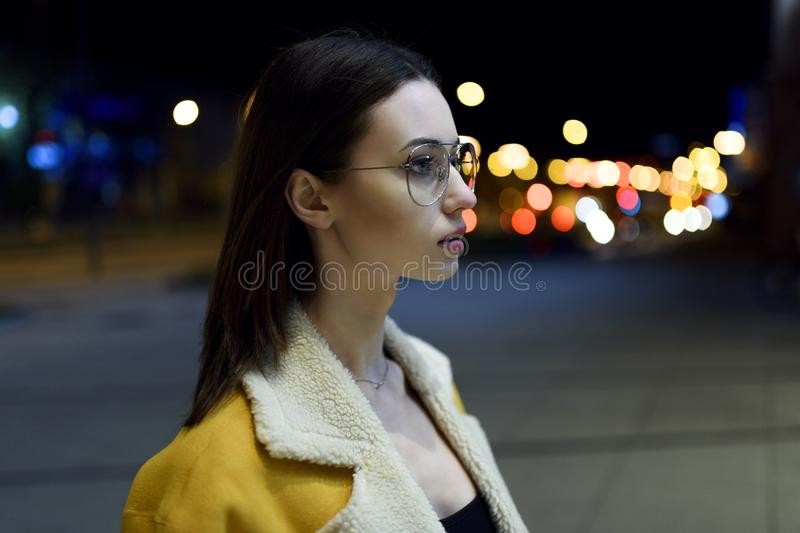 Porträt von Brunette in den Gläsern mit dem Gesicht gedreht zur Seite und durch Stadtzentrumlichter beleuchtet Womenswear-Mode stockfoto