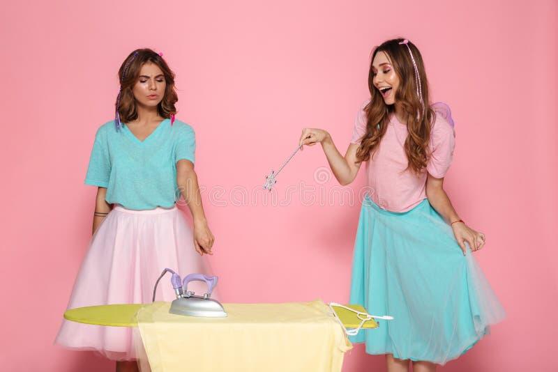 Porträt von, das zwei lustigen jungen Mädchen bügeln Kleidung ist stockfotos