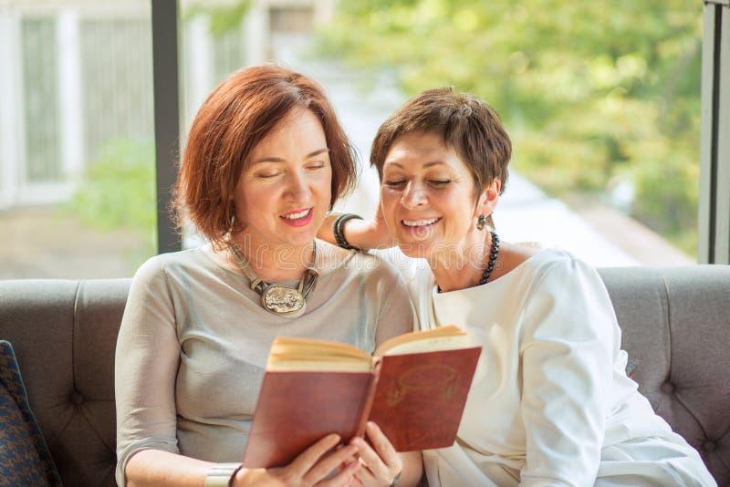 Porträt von den älteren Frauen, die zusammen ein Buch lesen lizenzfreies stockbild