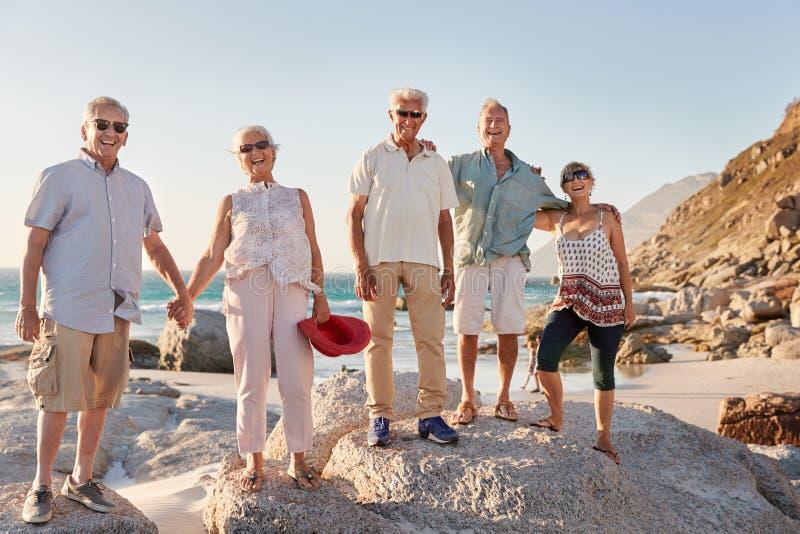 Porträt von den älteren Freunden, die auf Felsen durch Meer auf Sommer-Gruppen-Ferien stehen stockfotos