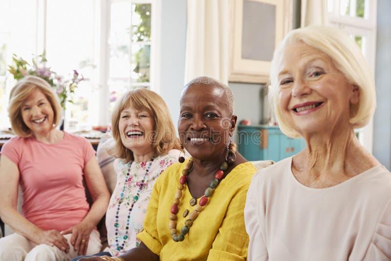 Porträt von den älteren Freundinnen, die auf Sofa At Home sich entspannen lizenzfreie stockfotografie
