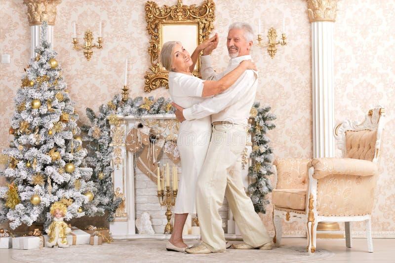 Porträt von den älteren Paaren, die nahe Weihnachtsbaum tanzen lizenzfreie stockfotografie