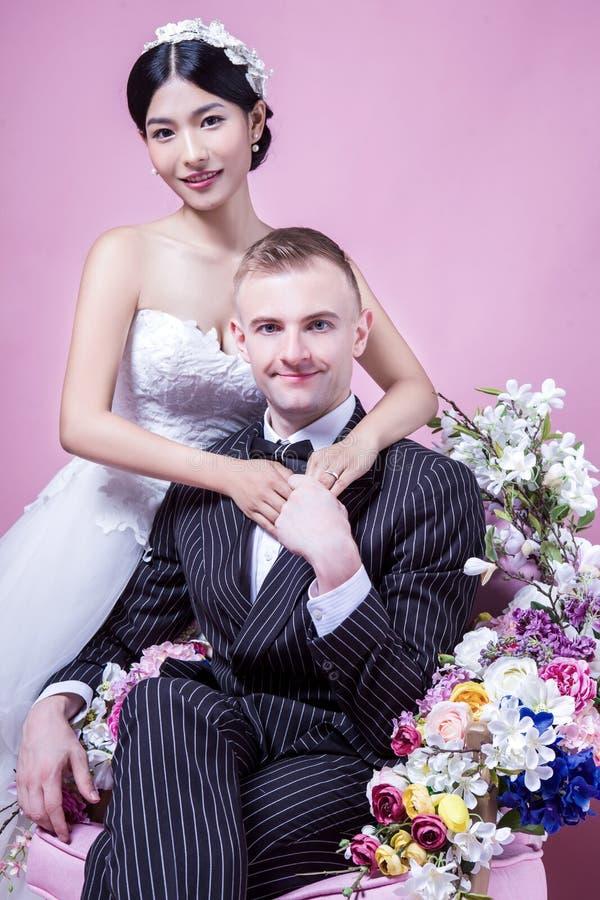 Porträt von den überzeugten Hochzeitspaaren, die gegen rosa Hintergrund sitzen lizenzfreie stockbilder
