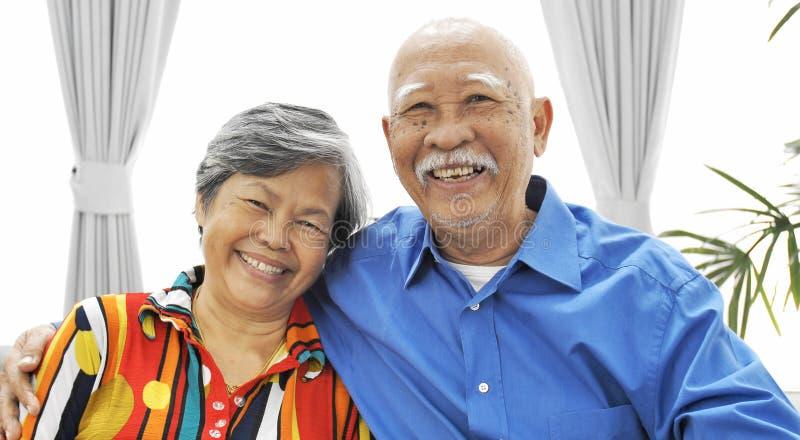 Porträt von den asiatischen älteren Paaren, die eine Kamera mit Lächelngesicht schauen stockbild