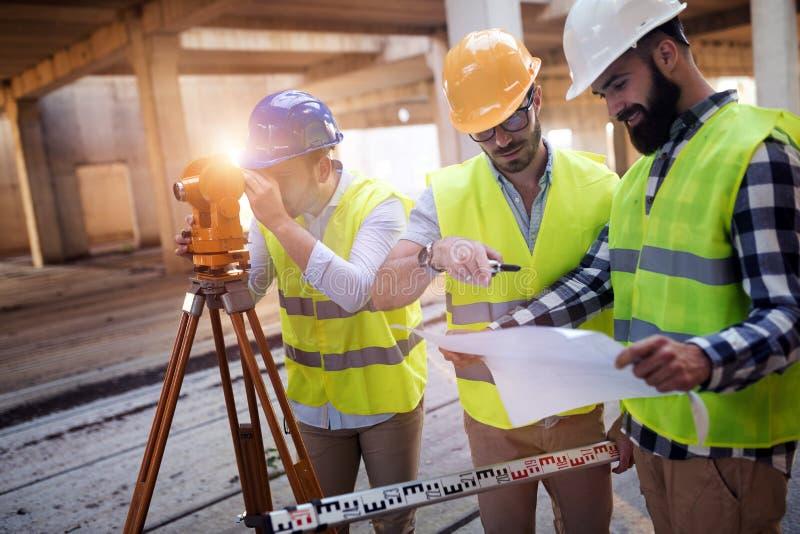 Porträt von den Bauingenieuren, die an Baustelle arbeiten stockbild