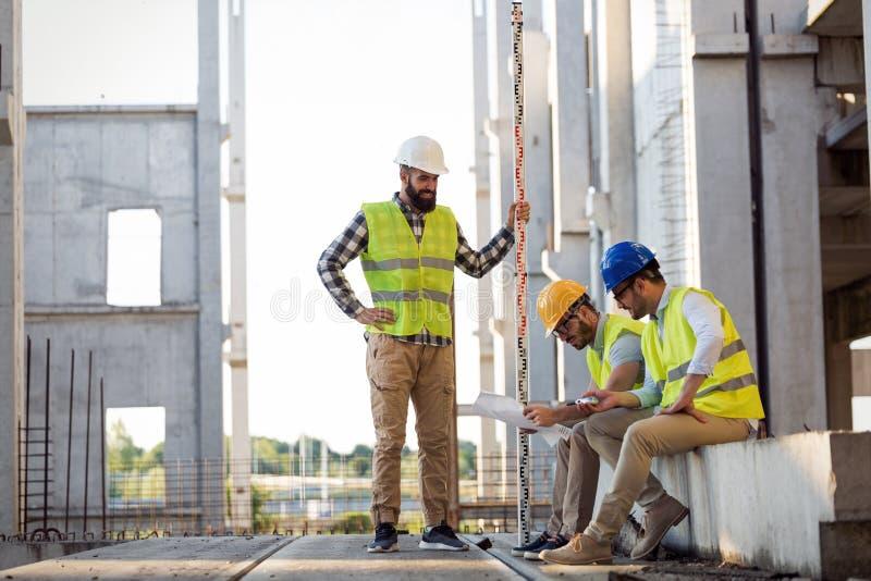 Porträt von den Bauingenieuren, die an Baustelle arbeiten lizenzfreie stockfotografie