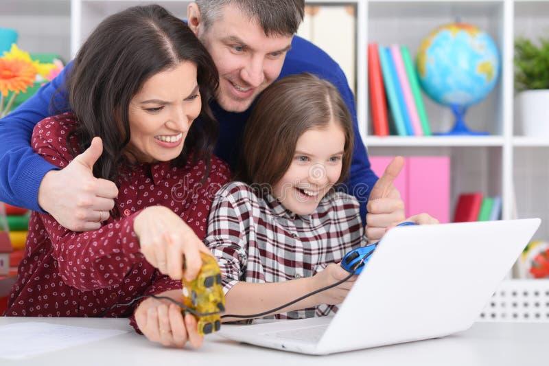 Porträt von den Eltern und von Tochter, die Computerspiel mit Laptop spielen stockfotos