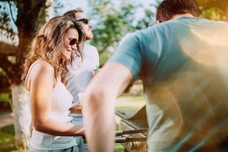 Porträt von den Freunden, die auf Grill während der Sommerzeit kochen stockfoto