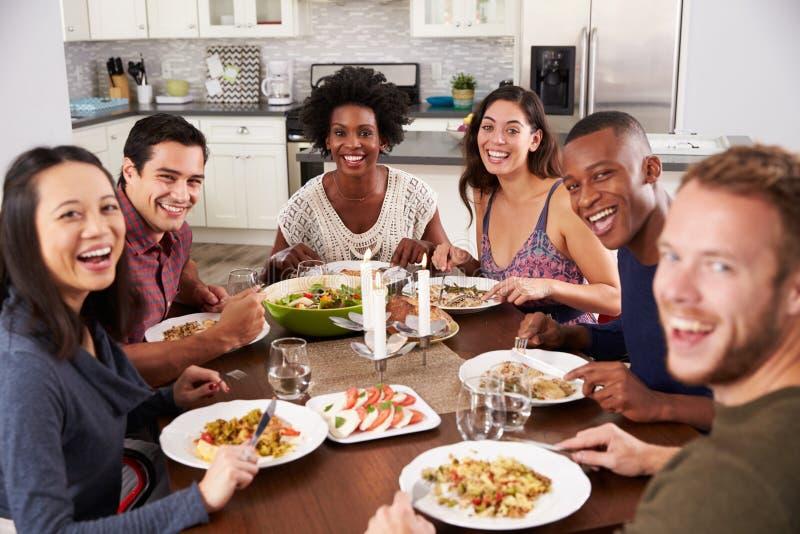 Porträt von den Freunden, die zu Hause Abendessen genießen stockfotos