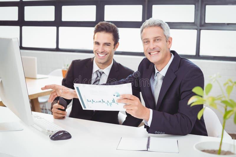Porträt von den Geschäftsleuten, die am Computertisch arbeiten stockfotos