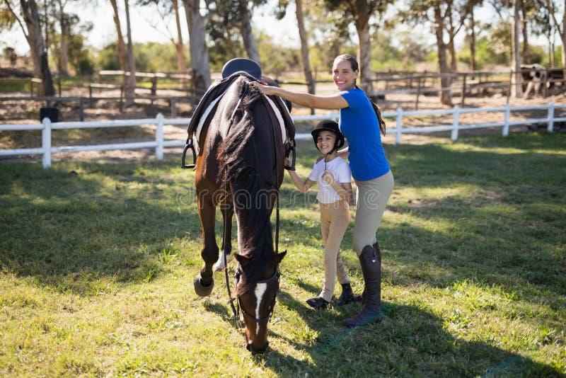 Porträt von den Geschwister, die Pferd bereitstehen lizenzfreie stockfotos