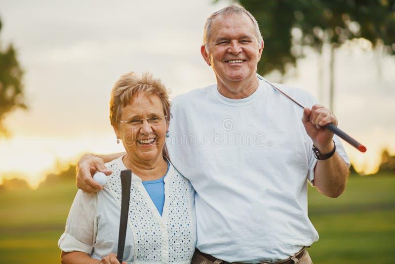 Porträt von den glücklichen älteren Paaren, die den aktiven Lebensstil spielt Golf genießen stockfotografie