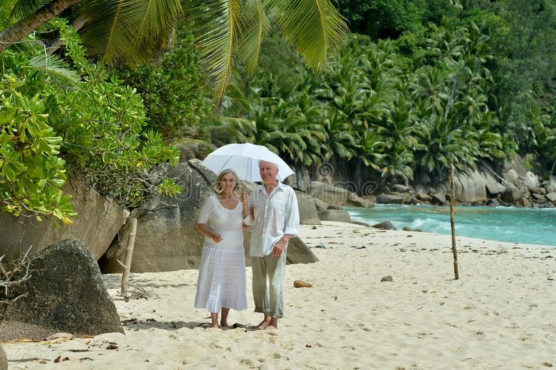 Porträt von den glücklichen älteren Paaren, die auf tropischem Strand mit Regenschirm stillstehen stockfotografie