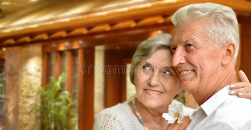 Porträt von den glücklichen älteren Paaren, die gegen unscharfen Hotelinnenhintergrund umarmen lizenzfreie stockbilder