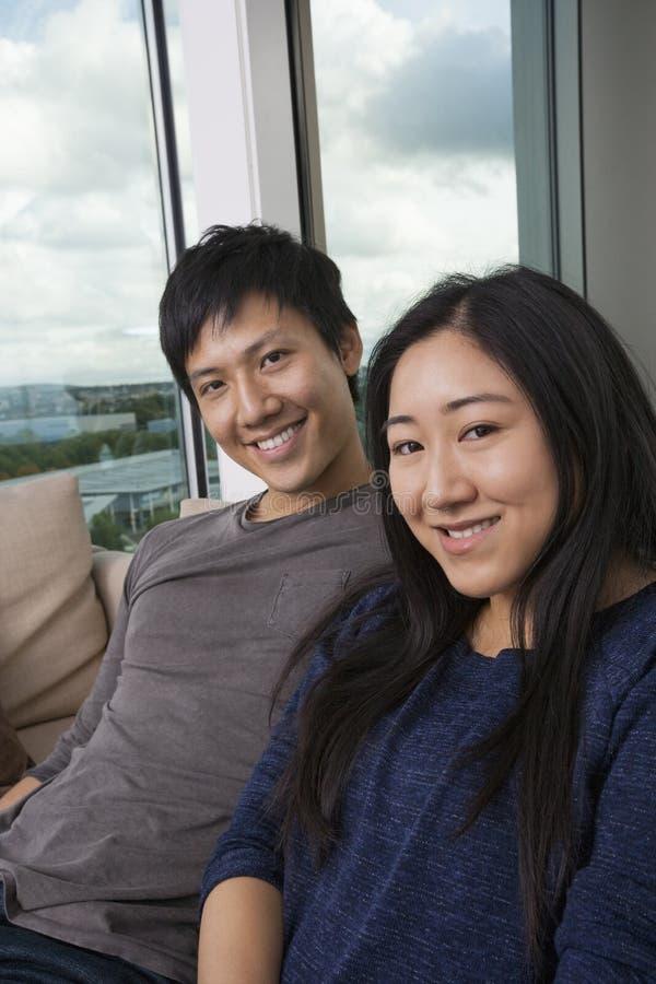Porträt von den glücklichen asiatischen Paaren, die zu Hause auf Sofa sitzen lizenzfreies stockfoto