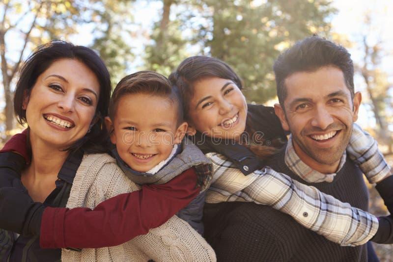 Porträt von den glücklichen Eltern, die draußen Kinder huckepack tragen stockbilder