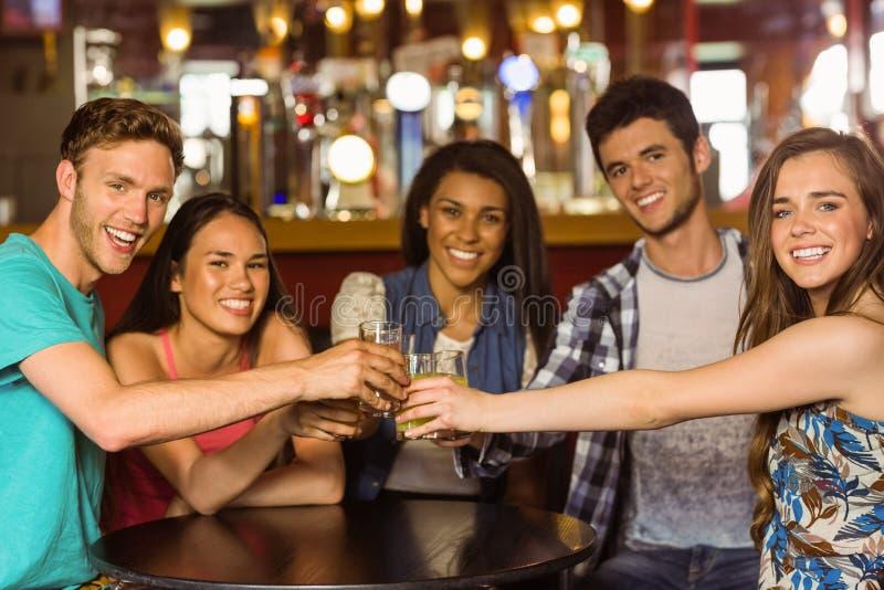 Porträt von den glücklichen Freunden, die mit Getränk und Bier rösten lizenzfreies stockfoto