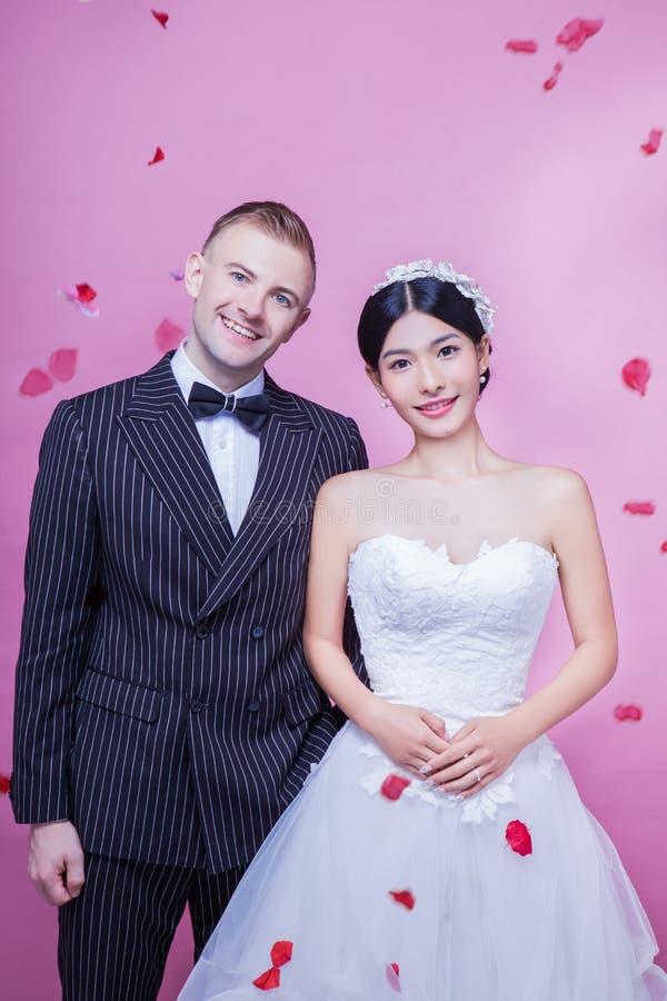 Porträt von den glücklichen Hochzeitspaaren, die gegen rosa Hintergrund stehen lizenzfreies stockbild