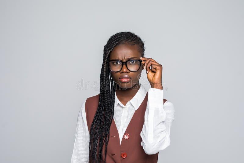 Porträt von den glücklichen jungen afrikanischen tragenden Gläsern der Geschäftsfrau, die Kamera über grauem Hintergrund schauend lizenzfreies stockfoto
