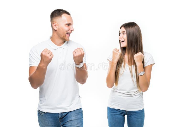 Porträt von den glücklichen jungen Paaren, die Erfolg mit den Händen in der Luft auf weißem Hintergrund feiern lizenzfreies stockfoto
