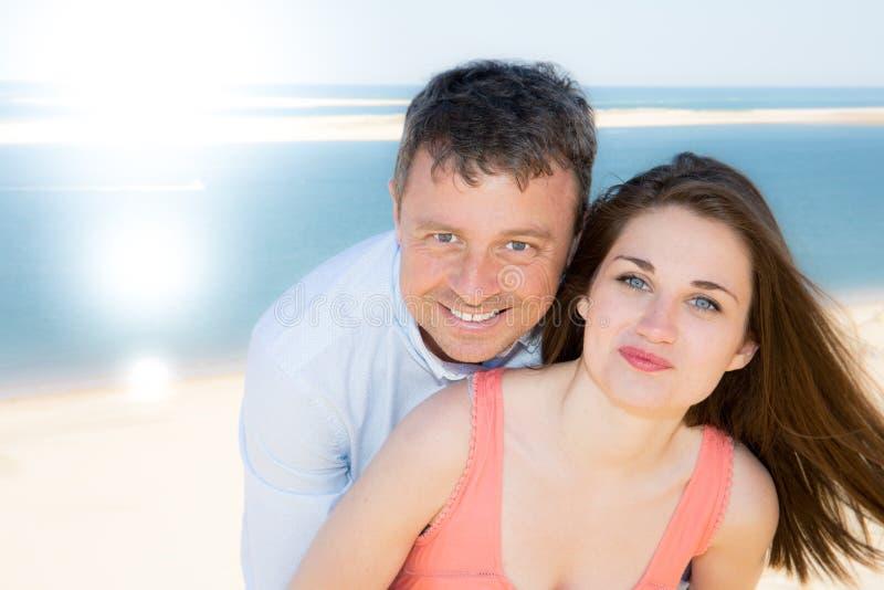 Porträt von den glücklichen jungen Paaren, die den Tag auf dem Strand während der Ferien genießen lizenzfreies stockfoto