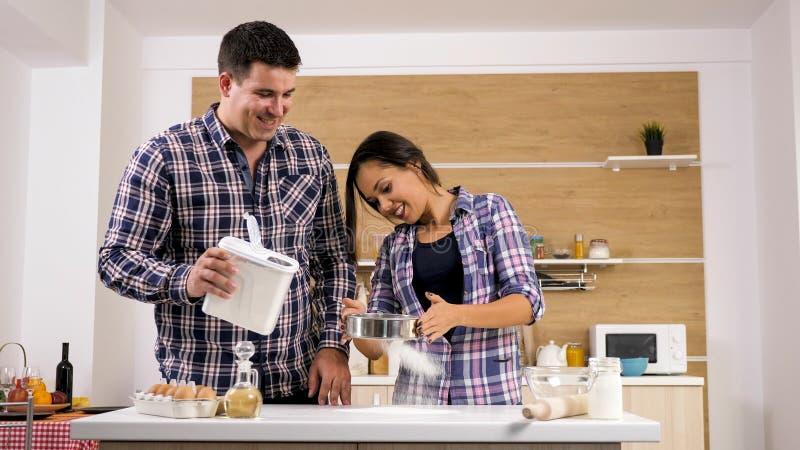 Porträt von den glücklichen jungen Paaren, die zusammen zu Hause in der Küche kochen stockfotos