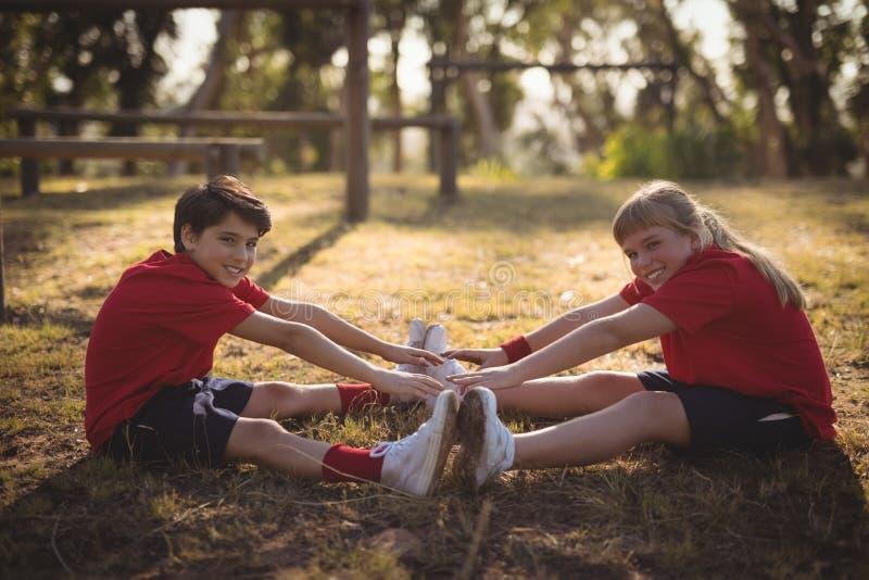 Porträt von den glücklichen Kindern, die Übung während des Hindernislaufs ausdehnend durchführen lizenzfreies stockbild