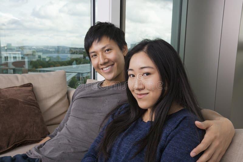 Porträt von den glücklichen liebevollen Paaren, die zu Hause auf Sofa sitzen stockfotos