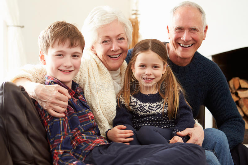 Porträt von den Großeltern, die auf Sofa With Grandchildren sitzen stockfotografie