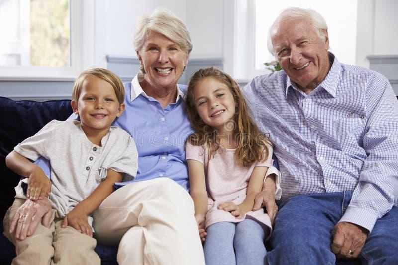 Porträt von den Großeltern und von Enkelkindern, die auf Sofa sitzen stockbild